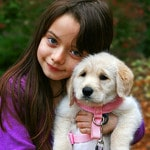 young girl leaning head on white puppy